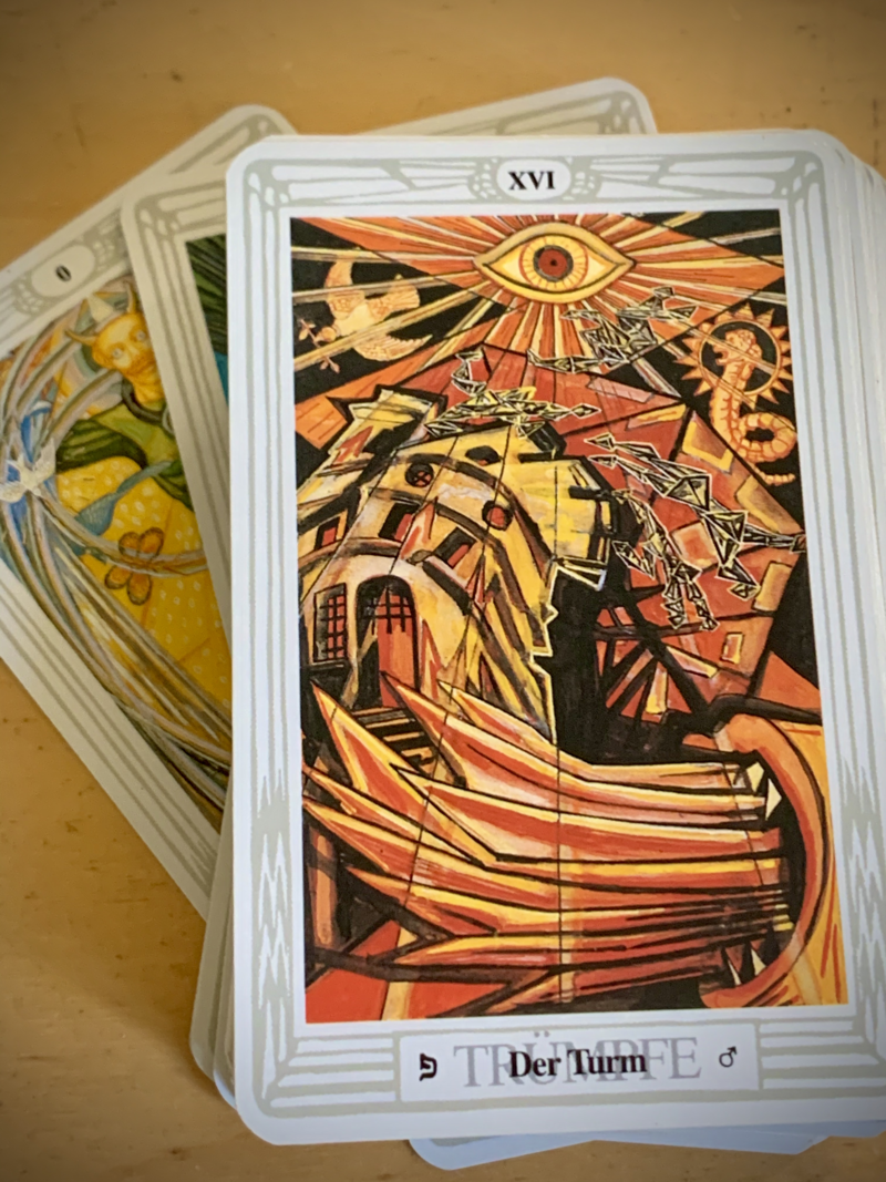 Shows a card deck with the illustrated card 'The Tower' on top. The card consists of an abstract drawing with bright flares, a collapsing building, consuming fire and an all seeing eye above. Behind the deck the card of the fool peeks out.